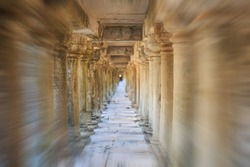 Viewed from the entrance, a zoom blur photo of ancient stone columns in a long temple passageway near Angkor Wat, Cambodia.