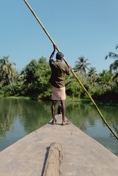 Views of an Indian man driving a boat in the Backwaters of Kerala on a sunny day. The sky is blue and there're palmtrees.