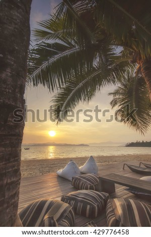 Views of sunrise with cushions and coconut palm trees on tropical beach background at Phayam island in Ranong province, Thailand. Happy summer holiday concept #429776458