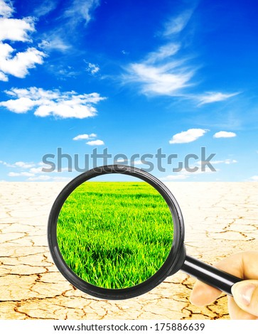 views of the desert with a magnifying glass on a background of green field with a blue sky