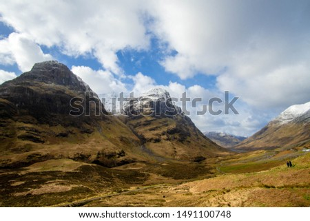 Views over the Glen Coe valley in winter, with snow topped peaks and blue ski peaking through the clouds