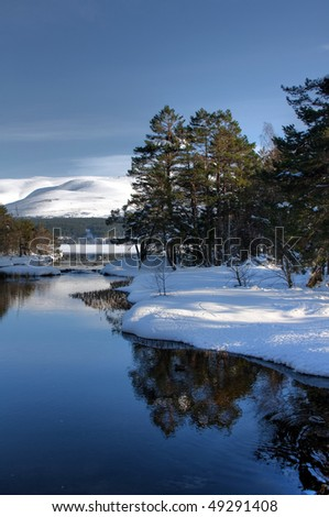 Views to the Cairngorm Mountains over Loch Morloch with snow on the ground