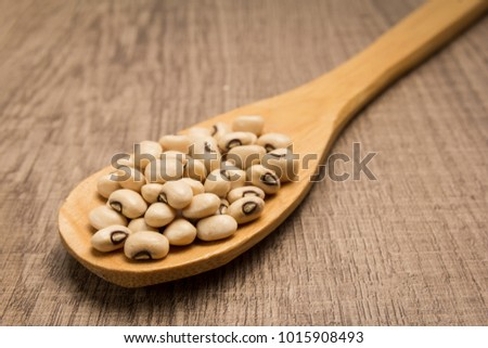 Vigna unguiculata is scientific name of Black Eyed Pea legume. Also known as Goat Pea, California Blackeye and Feijao Fradinho. Spoon and grains over wooden table.