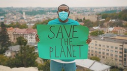 Vigorous ecology activist in respiratory mask striking to save the environment showing a Save the Planet poster on mountain top. Eco-action. Pandemic. Climate change.