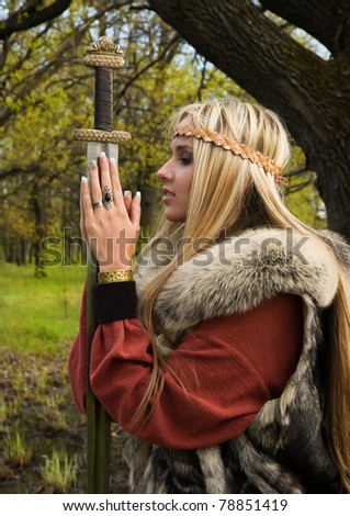 Viking girl warrior with sword in a wood