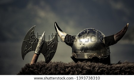 Photo of  Viking helmet with axe on fjord shore in Norway. Tourism and traveling concept