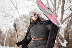 Viking in winter with a spear and a round shield of red-black color. A guy in a helmet and chain mail in the snow. A man in armor goes to battle