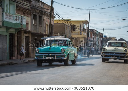 VILLA CLARA, CUBA - JULY 03, 2015: American vintage cars drives on the street in the countryside from Villa Clara