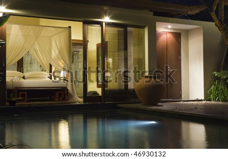 Villa in night illumination and pool before her
