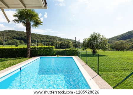 Villa with pool and surrounded by green lawn on a summer day. Nobody inside #1205928826