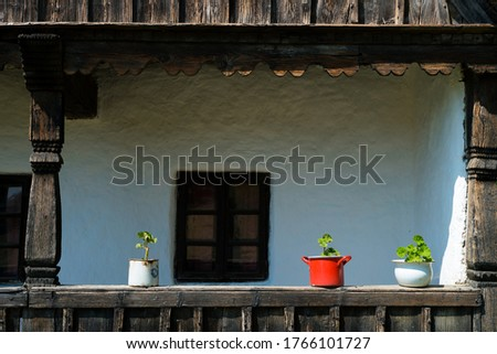 Village atmosphere - geraniums planted in red pots on the porch of an old house. Foto stock ©