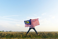 village boy waving Malaysia flag at paddy field