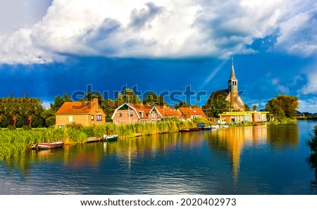 Village by the river on a cloudy day. Village river view. River village