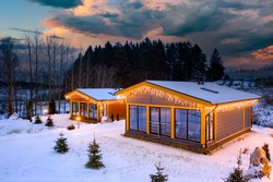 Village houses in winter weather. Two houses with panoramic windows in nature. Cottages next to forest. Country cottages at dawn. Country houses near winter taiga. Summer cottages covered with snow