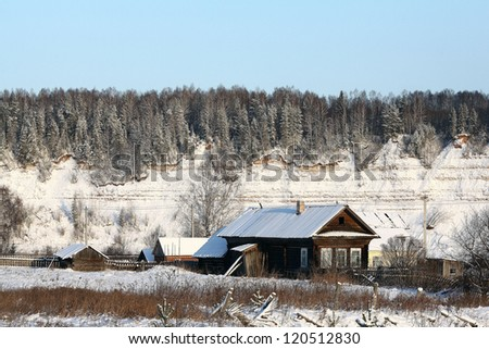 Village in winter, the snow-covered countryside, forest and wood houses