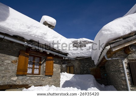 village of chalets covered with snow in mountain during winter