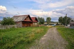 Village street in summer. Old wooden house with barn. Ancient village of Visim, Sverdlovsk region, Urals, Russia.