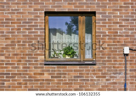 Village window with indoor flowers on red brick wall in mass rural home front view. Sunny summer day