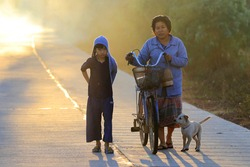 Village women carrying bicycles Ready girl With a small dog In the morning light