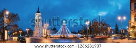 Vilnius, Lithuania. Christmas Tree On Background Bell Tower Belfry Of Vilnius Cathedral At Cathedral Square In Evening New Year Christmas Xmas Illuminations. Unesco World Heritage Site.