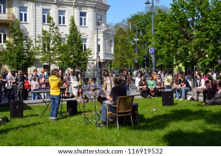 VILNIUS, LITHUANIA - MAY 19: Young unidentified musician play drums and other instrument and sign in street music day on May 19, 2012 in Vilnius. Free event.