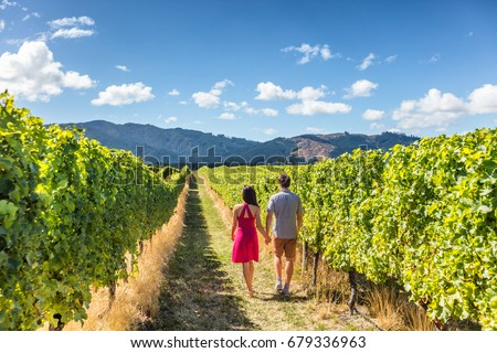 Vineyard couple tourists New Zealand travel visiting winery walking amongst grapevines. People on holiday wine tasting experience in summer valley landscape.