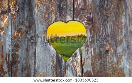 Vineyards along South Styrian Wine Road, a charming region on the border between Austria and Slovenia, seen through an old heart-shaped vintage wooden fence