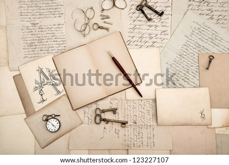 vintage accessories and open book over old letters and cards. nostalgic background