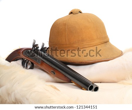 Vintage accessories for safari hunters. Tropical cork helmet and big pistol on a animal skin.