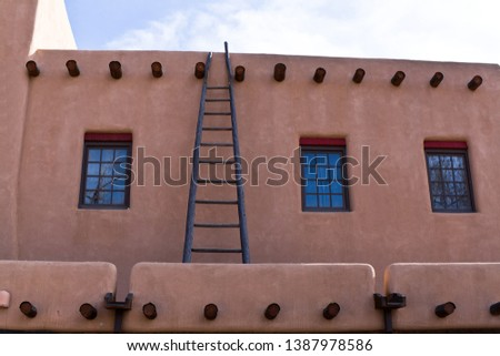 Vintage adobe house in traditional New Mexico design and old weathered wooden ladder