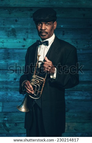 Vintage african american senior jazz musician with trumpet in front of old  wooden wall. Wearing 1da24c04f6bb