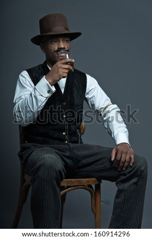Vintage afro america western cowboy man with mustache. Drinking whiskey. Sitting in wooden chair. Wearing brown hat. Cool tough guy.