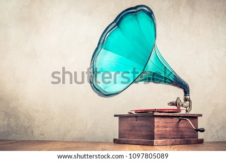 Vintage aged turquoise gramophone phonograph turntable on wooden table front concrete wall background. Retro old style filtered photo