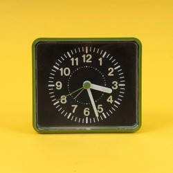 Vintage alarm clock. Analog green table clock. Retro antique alarm clock in bright yellow color background isolated.