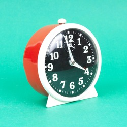 Vintage alarm clock. Analog red and white table clock. Retro antique alarm clock in bright green color background isolated.