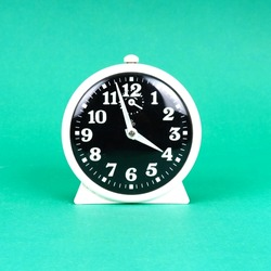 Vintage alarm clock. Analog table clock. Retro antique alarm clock in bright green color background isolated. Classic design. Vintage ticking clock with alarm bell.