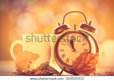 Vintage alarm clock and cup on yellow background with bokeh