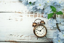 Vintage Alarm Clock And Flower Bouquet with space copy on wooden background