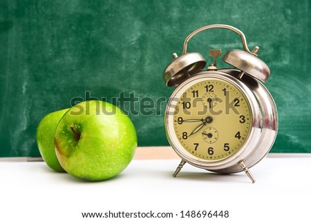 Vintage alarm Clock and green apples on teacher\'s table, green chalkboard in background.
