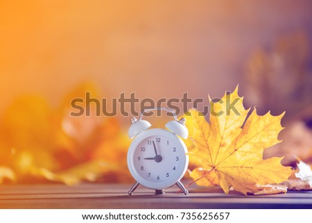 Vintage alarm clock and maple tree leaves on yellow wooden background with bokeh. Autumn season image style
