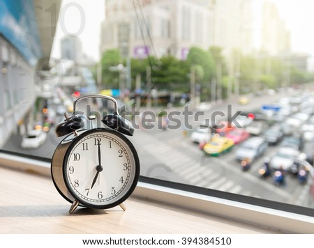 Vintage alarm clock at windows with abstract Blurred photo of traffic jam with rush hour on early morning, traffic transportation concept