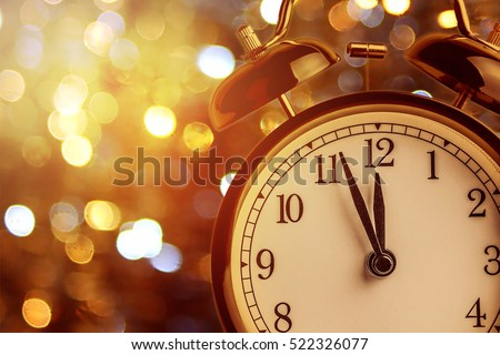vintage alarm clock is showing midnight. It is twelve o\'clock, christmas and bokeh, holiday happy new year festive concept on light bokeh background