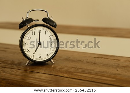 Vintage alarm clock on rustic wood table. Shows 7 o\'clock.