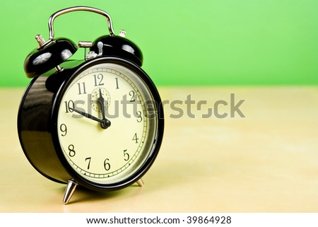 Vintage Alarm Clock on table on green background