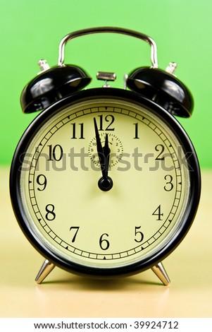 Vintage Alarm Clock on table on green background