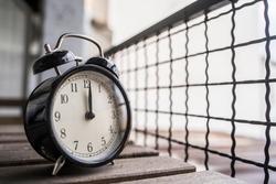 Vintage alarm clock with a buzzer showing exactly noon, closeup