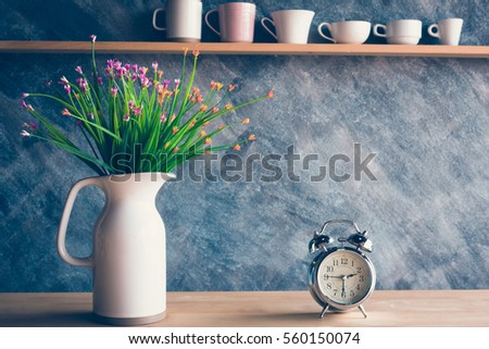 Vintage alarm clock with flower in jug on table and various cups background #560150074