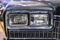 Vintage American car. Close-up of headlights and grille.