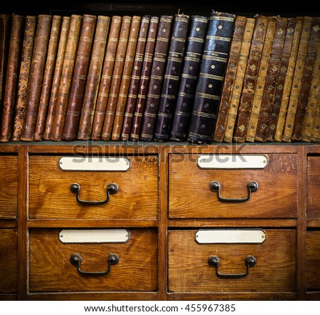 Vintage, antiquarian books on wooden cabinet. Retro background.
