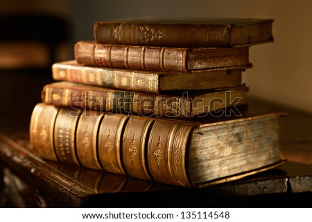 Vintage, antiquarian  books pile on wooden surface in warm directional light. Selective focus.